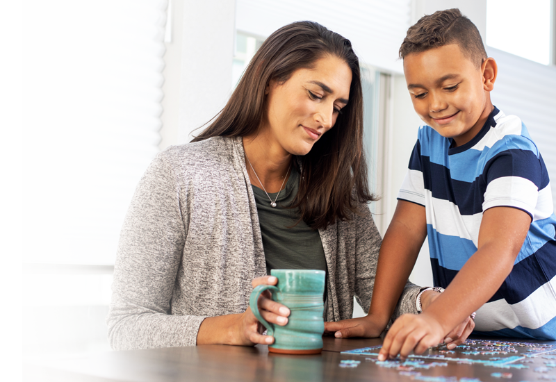 Promotional Image of a woman solving a puzzle with a child